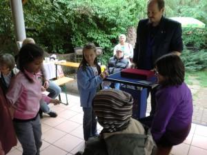 Kinder staunen über die Tricks des Zauberers Rainer Löffler
